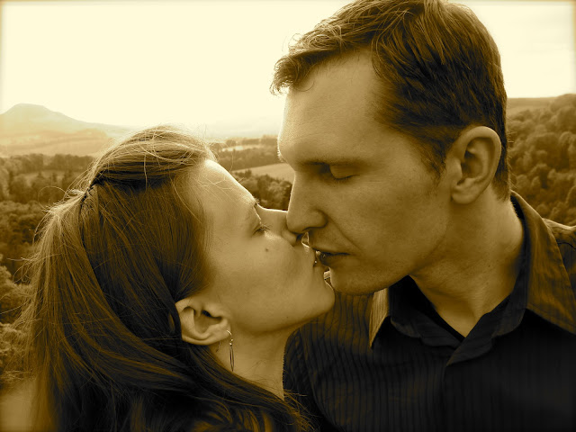 sepia photo of husband and wife kissing on a hilltop