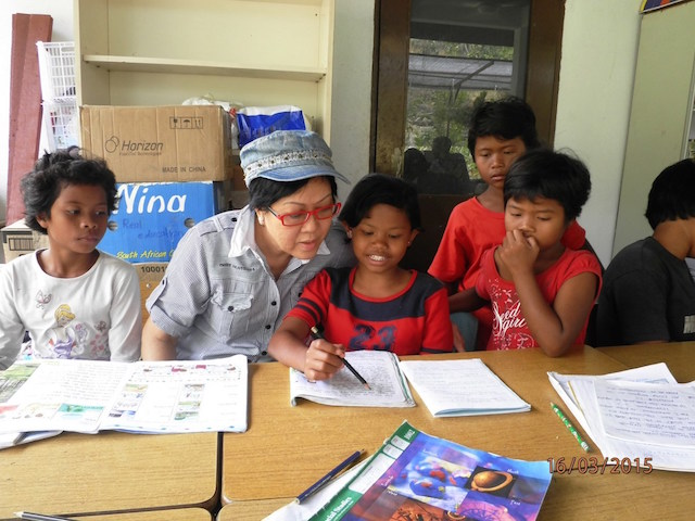 Dr Peggy C Wong helping the Bentong Orang Asli children to read their books