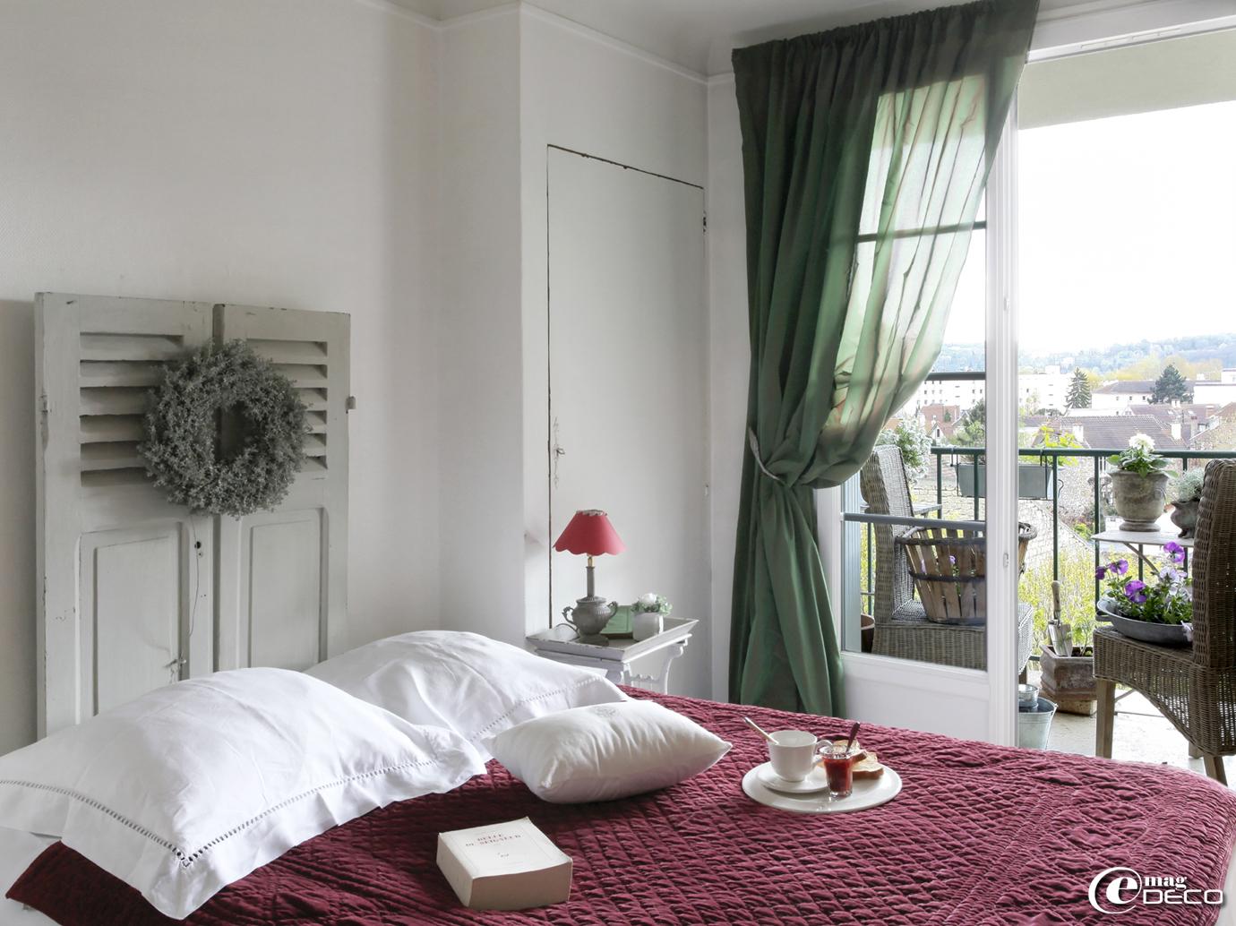 Dans une chambre, des persiennes décorées d'une couronne végétale se détournent en tête de lit, vaisselle et linge de lit 'Côté Bastide'