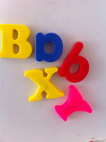Letters sticking on white surface spelling babyx