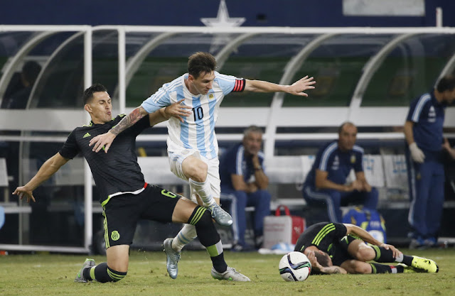 Football @ Argentina striker Lionel Messi will the ball to Jorge Torres of Mexico