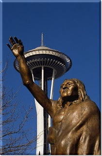 Statue of Seattle's Chief Sealth raising his arm in greeting with the Space Needle behind him