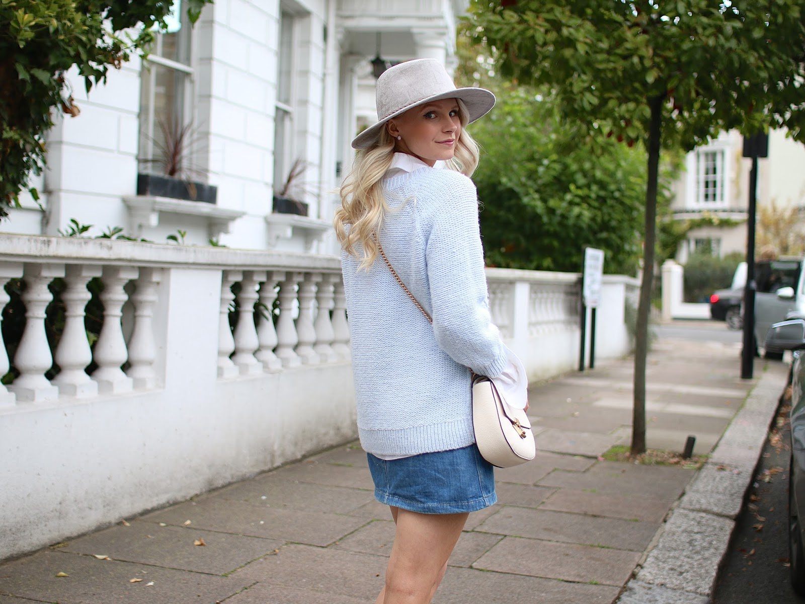 a blogger wearing an all blue outfit and chloe drew dupe purse looks back at the camera in beautiful london, notting hill