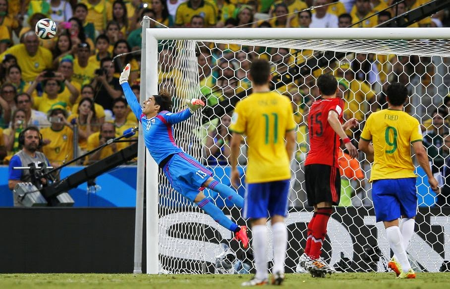 Mexico's goalkeeper Guillermo Ochoam, left, dives at a wide shot on the goal during the group A World Cup soccer match between Brazil and Mexico at the Arena Castelao in Fortaleza, Brazil, Tuesday, June 17, 2014.
