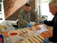 Col·laboradors preparant el pa amb tomàquet