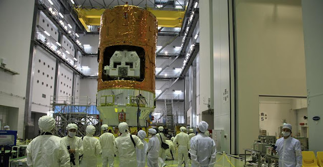 A crowd of media reporters photograph the fully integrated HTV-5 spacecraft at the Tanegashima Space Center. Photo Credit: JAXA