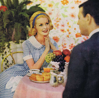 A simply lovely breakfast scene from 1960, featuring a woman rapturously in love, wearing  blue and white gingham dress and lovely blue hair bow. Her makeup is flawless, and breakfast perfect, indicating that she has likely been up for hours.