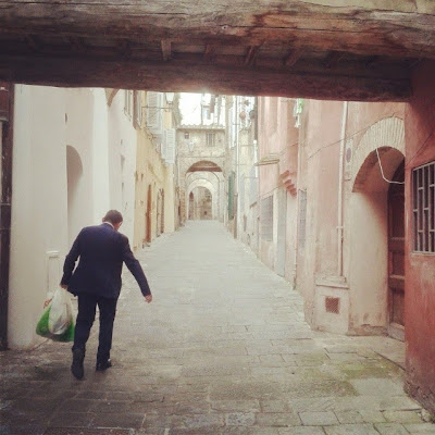 a business man walking through Siena with filled shopping bags