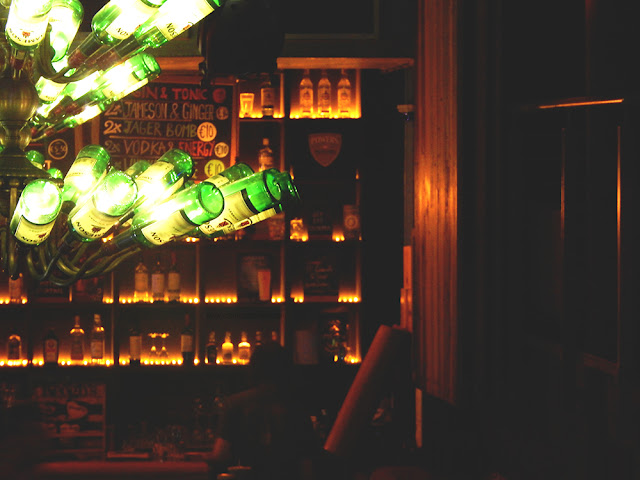 Jameson bottles glowing over a bar.