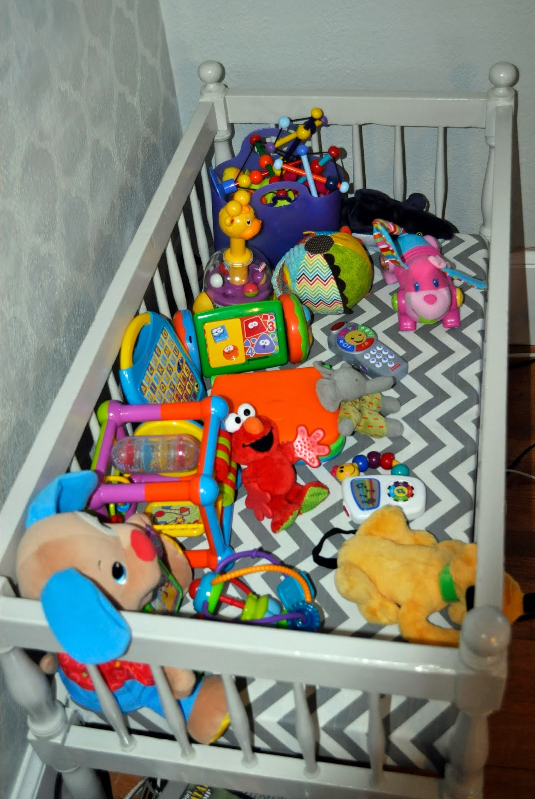 grey vintage crib turned into a toy chest with chevron fabric cushion