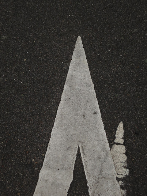White arrow on tarmac path with remains of old arrow showing how the route has changed