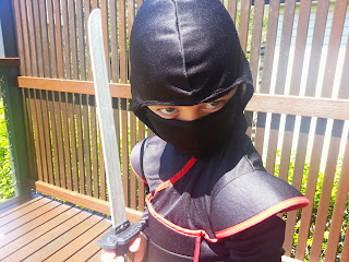 Photo of young boy in black and red ninja outfit