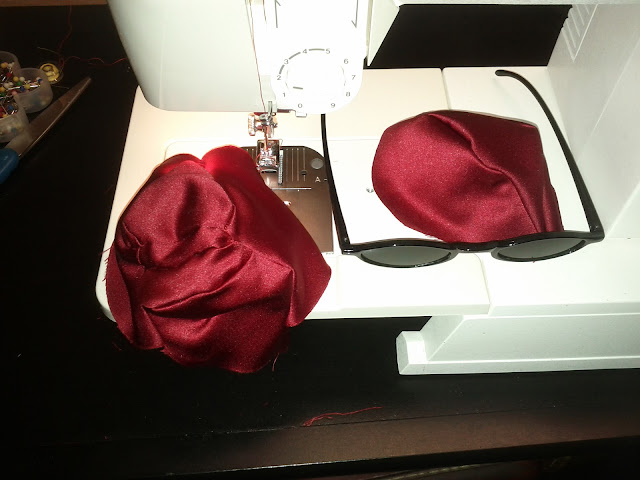 Red satin fabric starting to be sewn into a ball shape sits on a sewing machine with black sunglasses nearby.