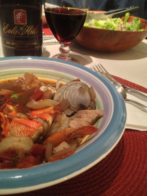 Table setting wth cioppino, red wine and salad