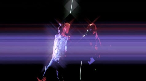 Maya and Aiji perform with starburst lighting effects.