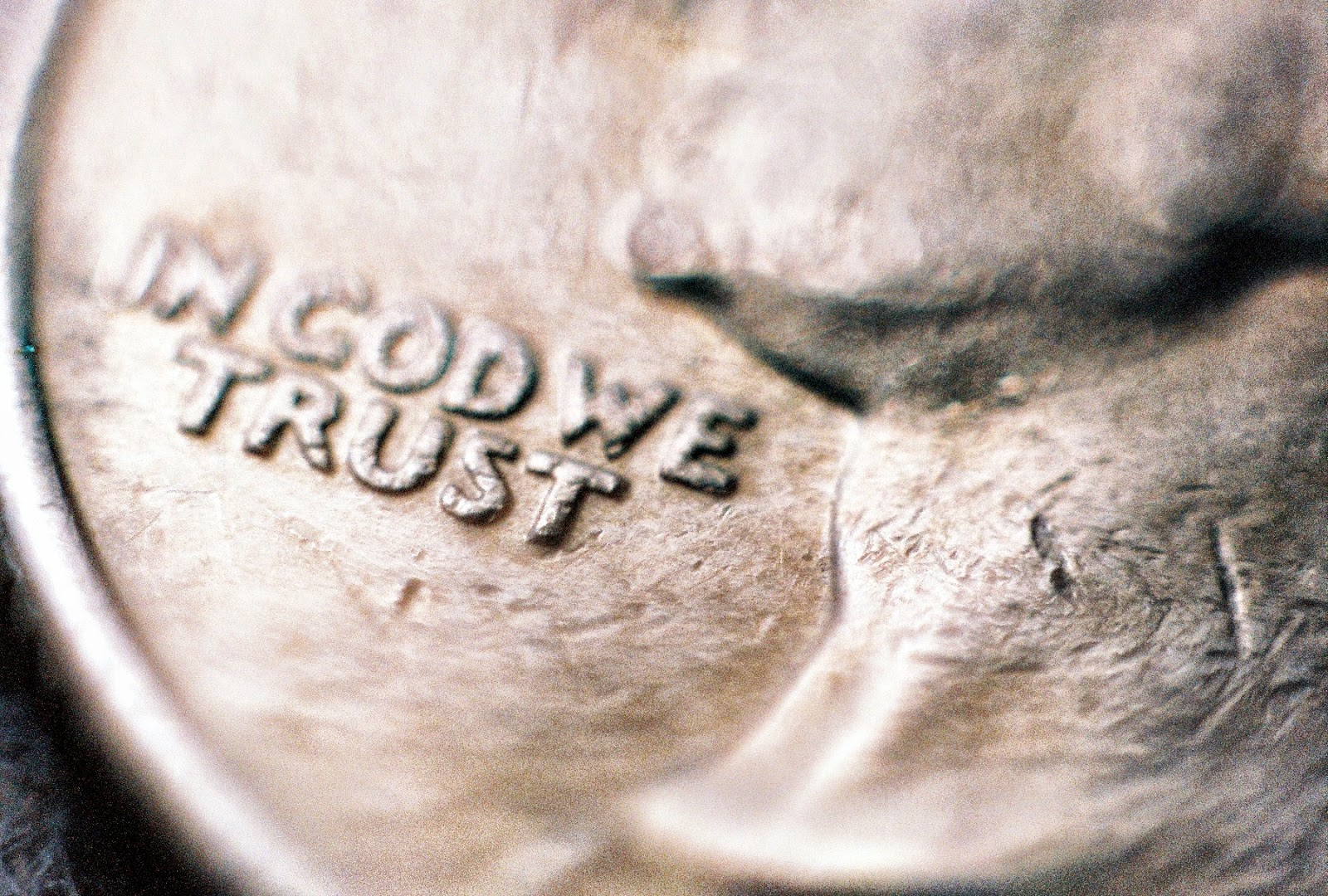 """In god we trust"" by Aaron van Dorn Partial photo of a quarter, emphasising the phrase ""In god we trust""."