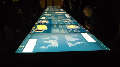 A bank of touchscreen tables with world maps and rights violations