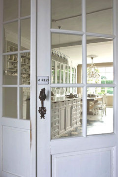 White glass door leading to kitchen with a small sign that says tirez above the knob in a mansion in Belgium