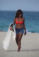 Claudia Jordan arriving at a beach in a red bikini top and short denim shorts