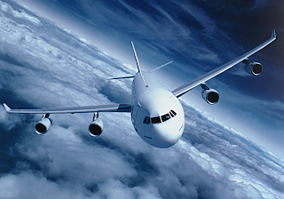 Close-up photo of a plane hovering over the clouds in the sky