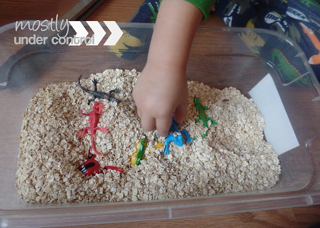 oatmeal sensory bin with lizards
