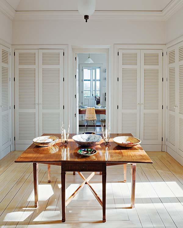 espacio cuadrangular blanco lleno de armarios con mesa sencilla  central