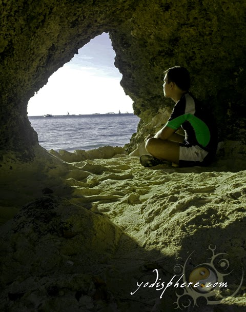 hover_share Solitary man in a cave looking out at the beach