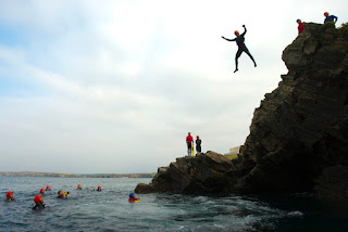 Man jumping off a cliff into deep water