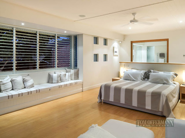 Photo of large modern bedroom with sitting area by the window