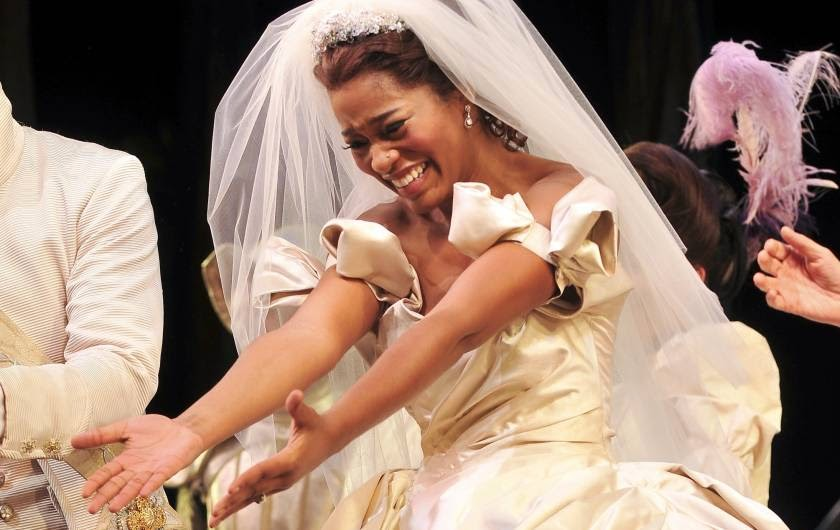 Keke Palmer in a wedding gown crying happy tears with her arms outstretched