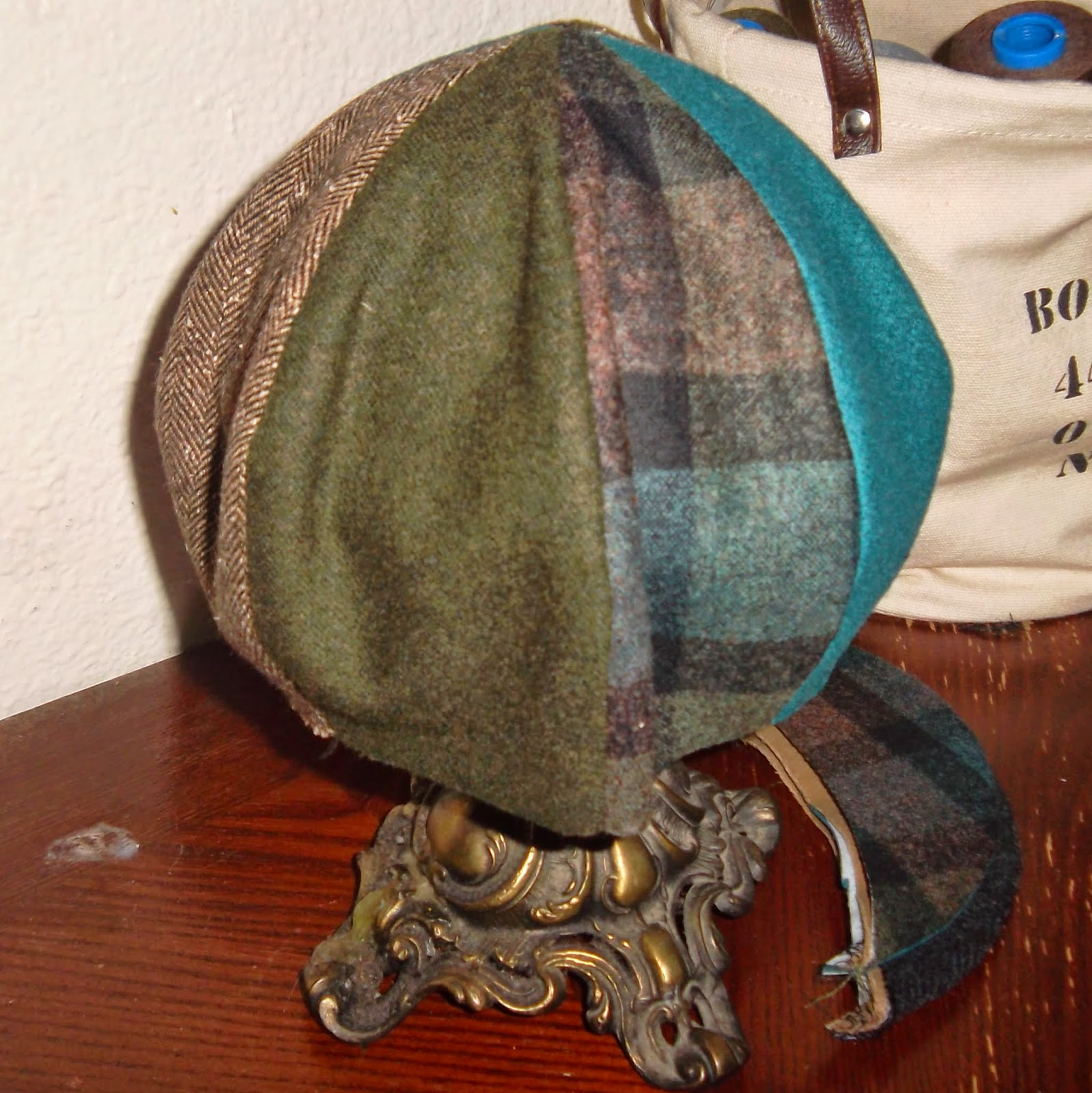 Eight-paneled crown of hat draped over metal hatstand. From left to right, the four panels visible in photo are brown houndstooth, dark-green solid, green-and-brown plaid and teal solid. A brown-and-green plaid, crescent-shaped bill is on tabletop at base of hat-stand. A second bill, beneath it, is of black herringbone.