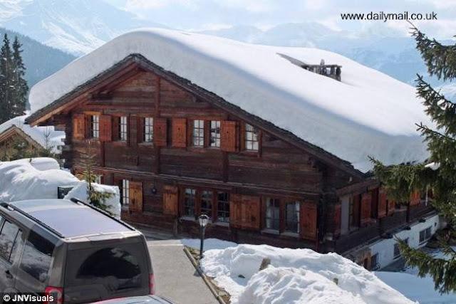 Casa chalé suizo de madera en la montaña nevada
