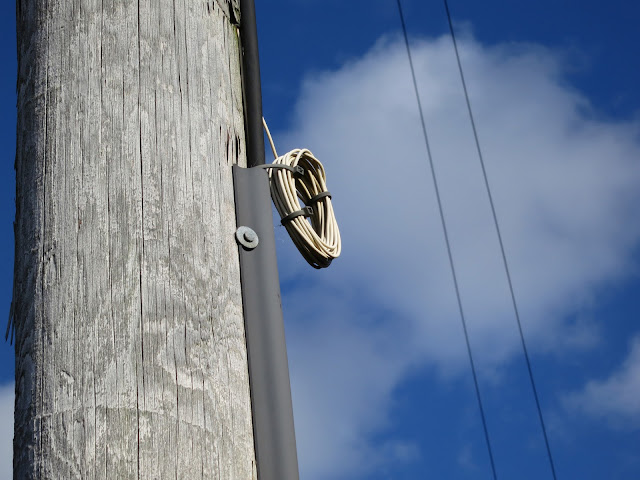 Telegraph pole, loop of wire, overhead wires, blue sky and cloud