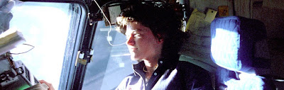 Astronaut Sally Ride enjoys the bright light and iew from a window of the Space Shuttle Challenger