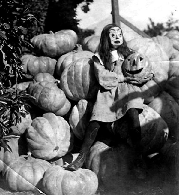 fotografia antigua de niña con mascara entre calabazas en halloween