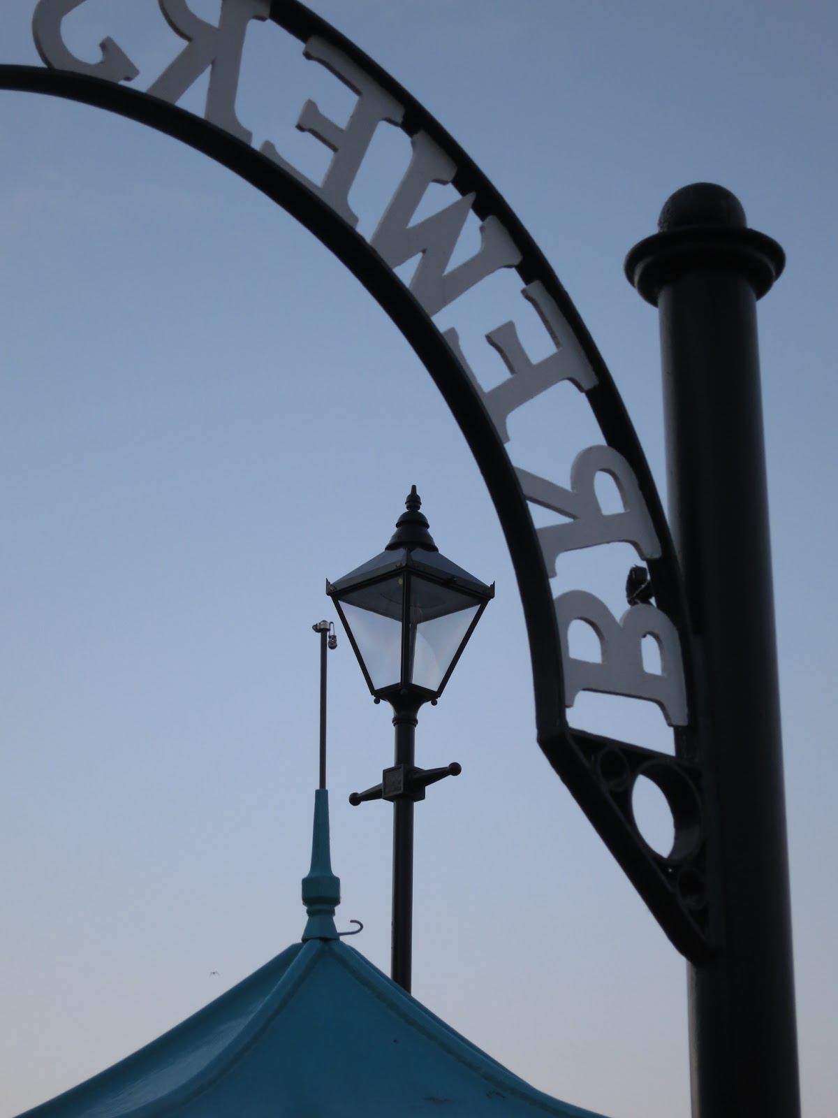Arch, lampost and pole on kiosk for boat trips