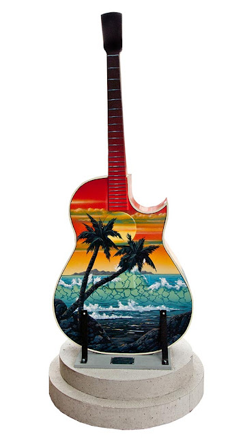 downtown Orillia outdoor art festival featuring guitars painted by local artists, this guitar has a sunset scene from Hawaii including palm trees