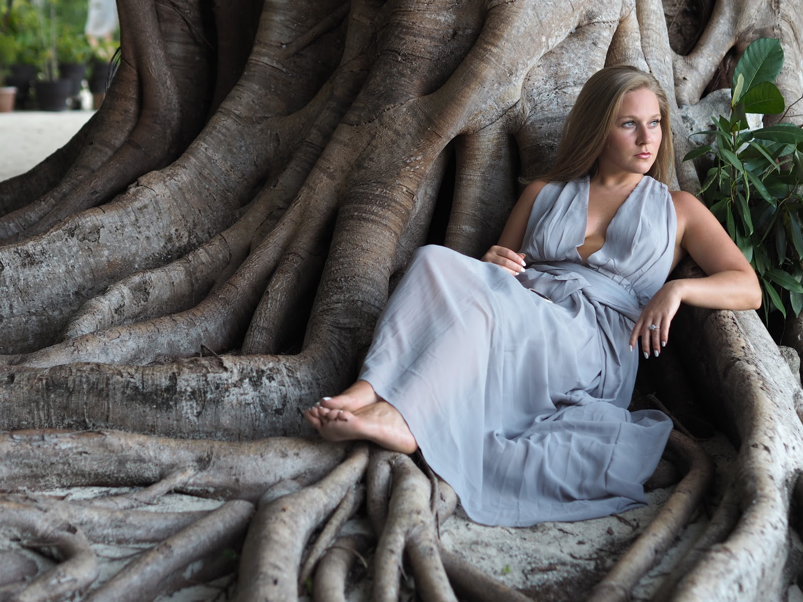 Katie Matthews, Blonde Girl wearing Grey dress under huge tree roots