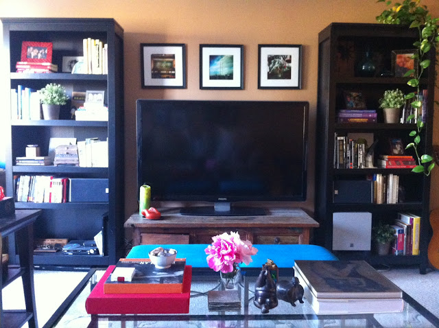 Living room before and after, Coffee table before and after, before and after, coffee table style, coffee table styling, coffee table design, coffee table vignette, bench seats, velvet bench seats, turquoise bench seats, bookshelf design, bookshelf vignette, pink flowers, pink peonies, fat yoga, coffee table books, large TV, book shelves next to TV, vintage TV stand, patterned pillows, small l-shape couch, trellis rug, lattice rug, side table vignette, horn lamp, sheep skin throw, brown club chair, glass knot, iron and glass coffee table, living room design, succulent, made her look, madeherlook.net, madeherlook.blogspot.com