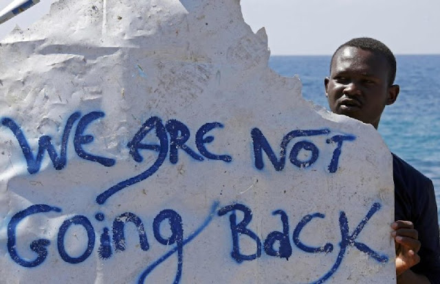"""A migrant holds a banner """" We are not going back"""""""