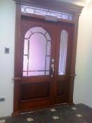 Puertas principal de laurel con cornizas y tapamarcos y vidrio decorado