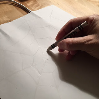 Drawing a white spider web onto a white craft bag with a white crayon