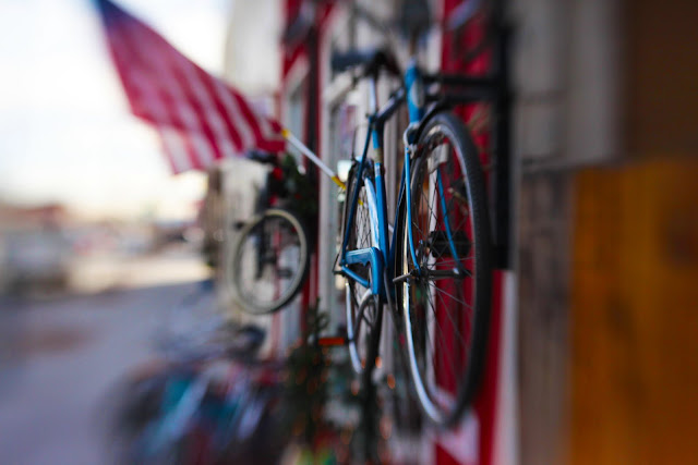 An old blue bike and an American flag hanging outside a bike shop in Denver. Shot with a Lensbaby Composer.