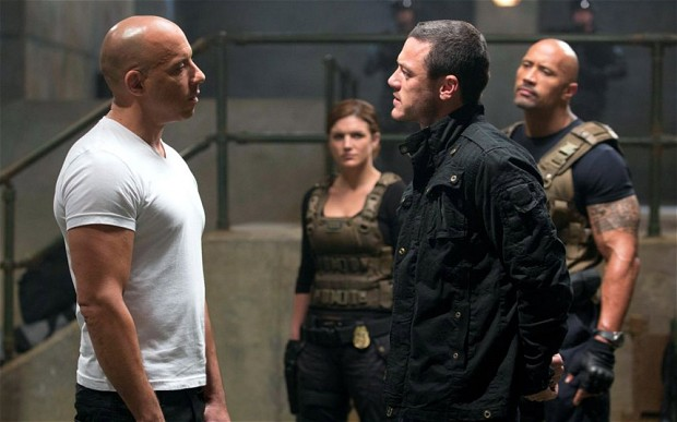A face-off scene between Dom and the villain Owen Shaw with Hobbs looking on
