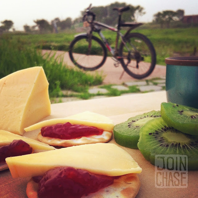 Cheese, crackers, jam, kiwi, coffee, and a bike in South Korea.