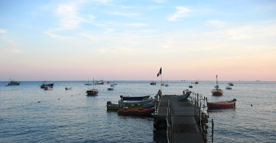 A pier and boats on the sea with a pinky blue sunset sky