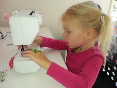 peuter achter de kindernaaimachine