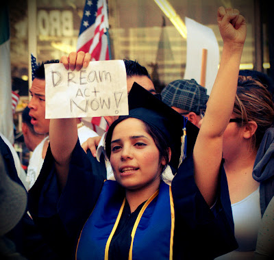 Graduate holds sign reading 'DREAM Act Now!'