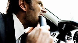 A man in a suit bites his car's steering wheel in frustration.