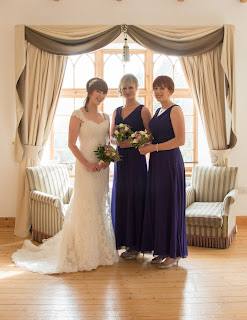 Bride in lace gown with her two bridesmaids in purple gowns with wedding hairstyles holding bouquets